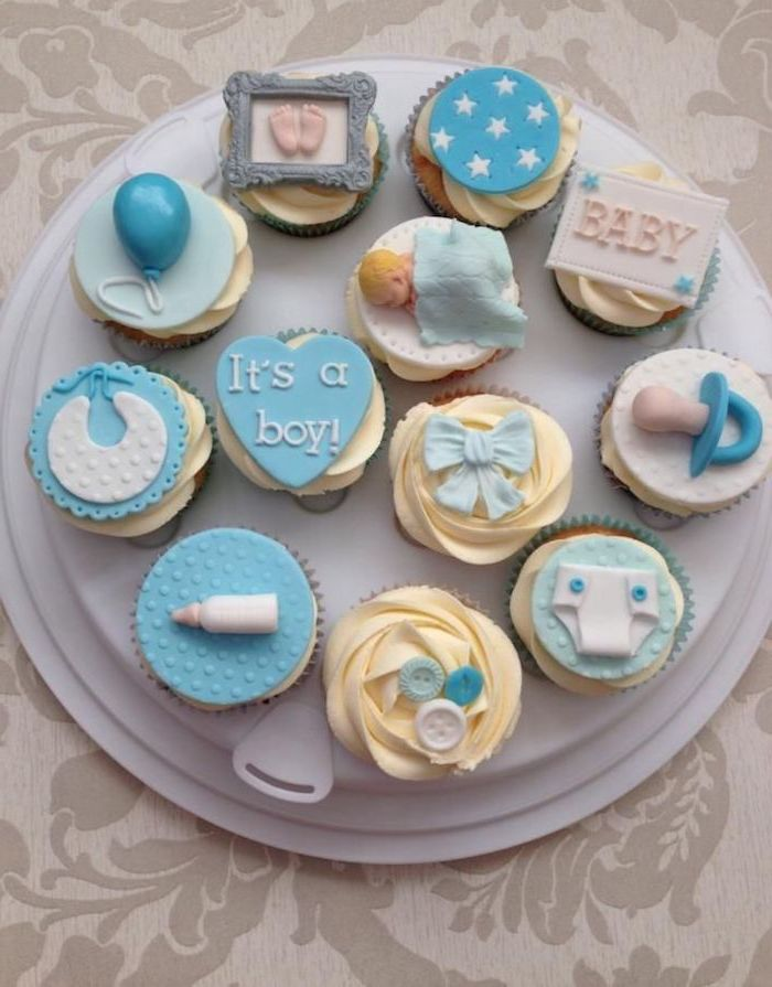 dummy and bib, baby bottle and balloon, little footprints and buttons, nappy and a sleeping baby figurine, all made from fondant, decorating a dozen of cupcakes