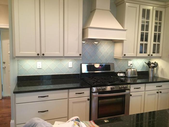 baby blue arabesque backsplash, with white joints, near white kitchen cabinets and drawers, smooth black counter top
