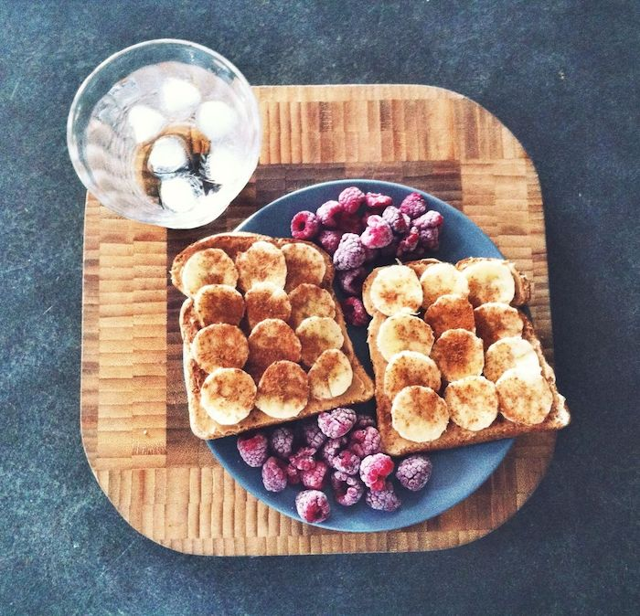 ice water in a clear glass, placed on a large wooden cutting board, near a blue round plate, with two pieces of toast, covered with banana slices and cinnamon, and accompanied with frozen raspberries, simple breakfast ideas