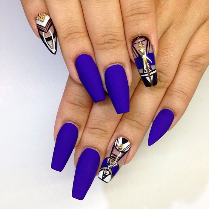 eight long coffin shaped nails, on two hands, placed on a white surface, five of the nails are painted in a vivid violet, matte nail polish, the other three are clear, and decorated with geometric motifs, and gold rhinestones