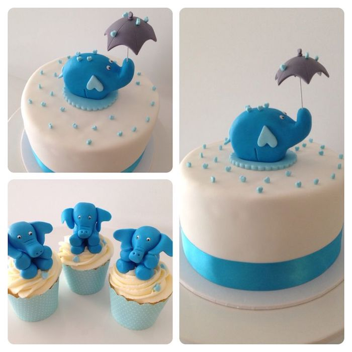 umbrella in grey, held by a small blue elephant figurine, topping a smooth white cake, with blue sprinkles, and a shiny blue bow, elephant baby shower cake, and three elephant cupcakes