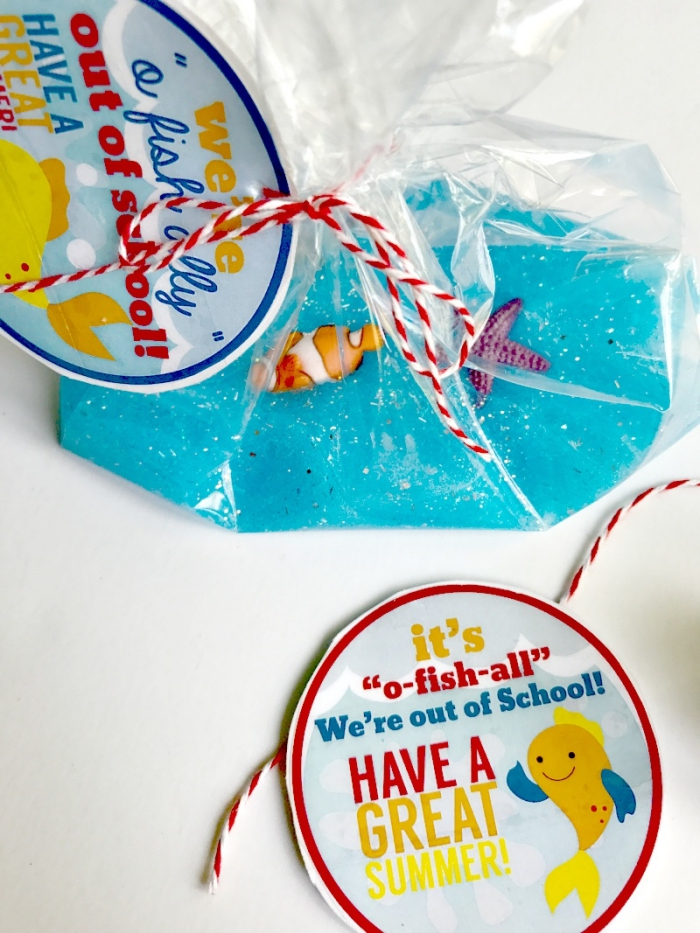 labels with colorful writing, and a drawing of a cartoon fish, tied to a clear plastic bag, containing ocean-inspired slime, how to make slime with shaving cream, glitter and tiny plastic fish ornaments