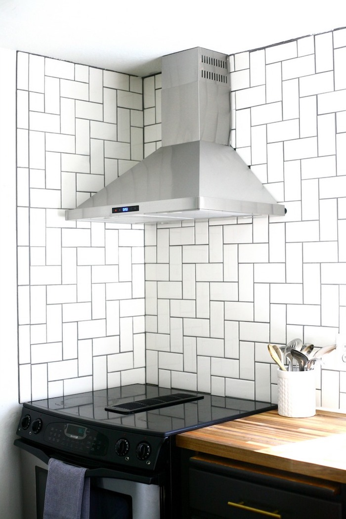 contrasting herringbone backsplash tiles, with black joints, near a glossy black oven, and a metal extractor hood