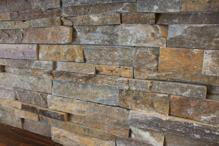 close up of a stacked stone backsplash, made from uneven grey, brown and beige pieces of stone, near a dark wooden surface