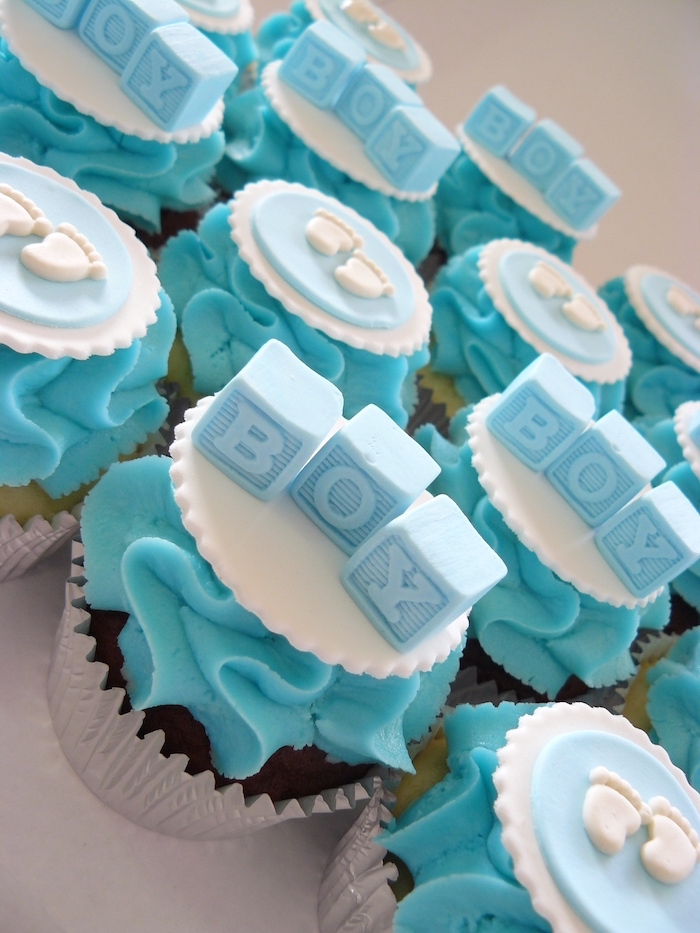 baby shower cakes for boys, cupcakes with turquoise frosting, decorated with white and blue fondant shapes, little feet and alphabet blocks spelling boy