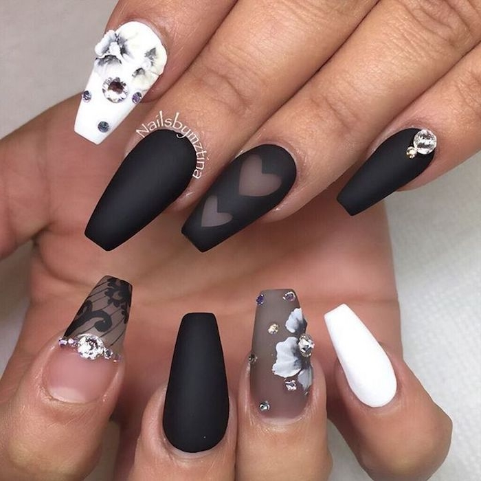 sheer and opaque nail polish, in black and white, on a set of fake nails, decorated with grey flowers and rhinestones