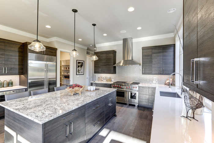 spacious kitchen with laminate floor, grey and dark brown cabinets, and a large marble countertop, with three hanging lamps, and several inbuilt ceiling lights