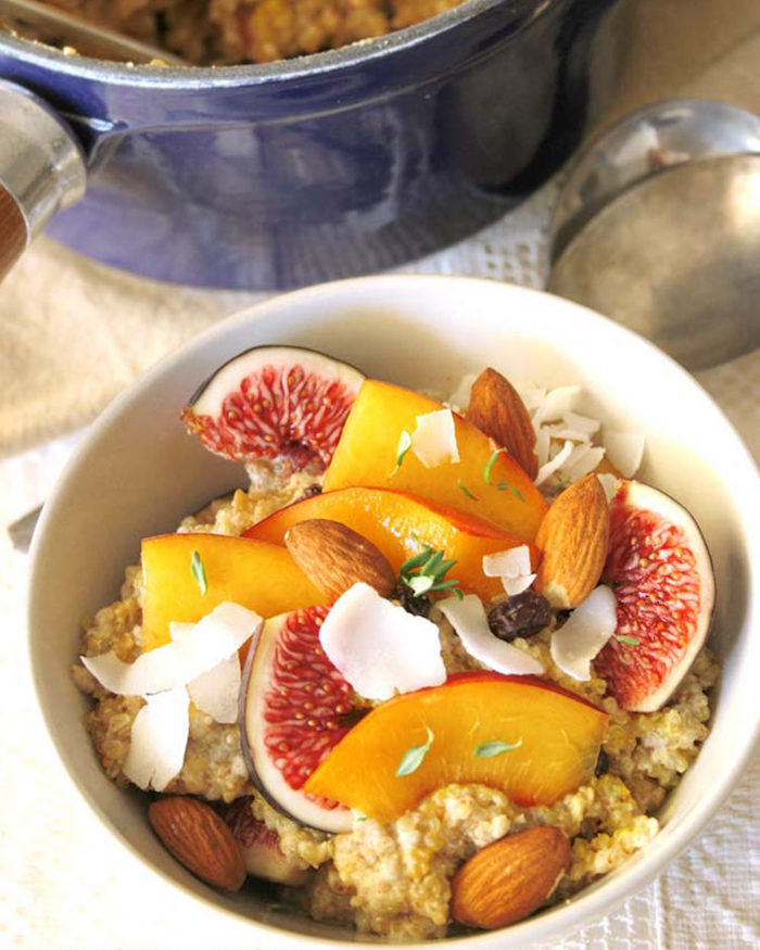 flakes of coconut and almonds, peach and fig slices, topping a bowl of porridge, low calorie breakfast, blue pan with more porridge