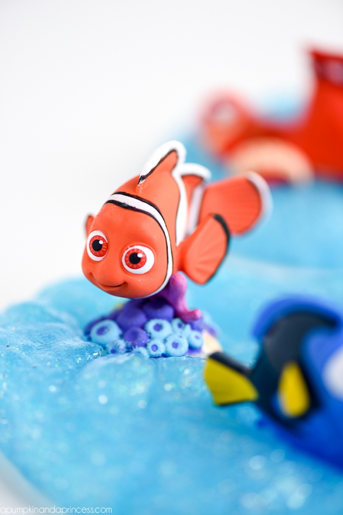 finding nemo-inspired, slime recipe without borax, blue sparkly goo, with fine silver glitter, decorated with several cartoon fish figurines