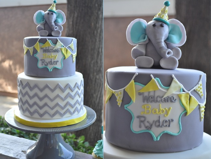 party hat on a small elephant figurine, made from grey and blue fondant, topping a grey cake, elephant baby shower cake, decorated with yellow details, and tiny fondant flags