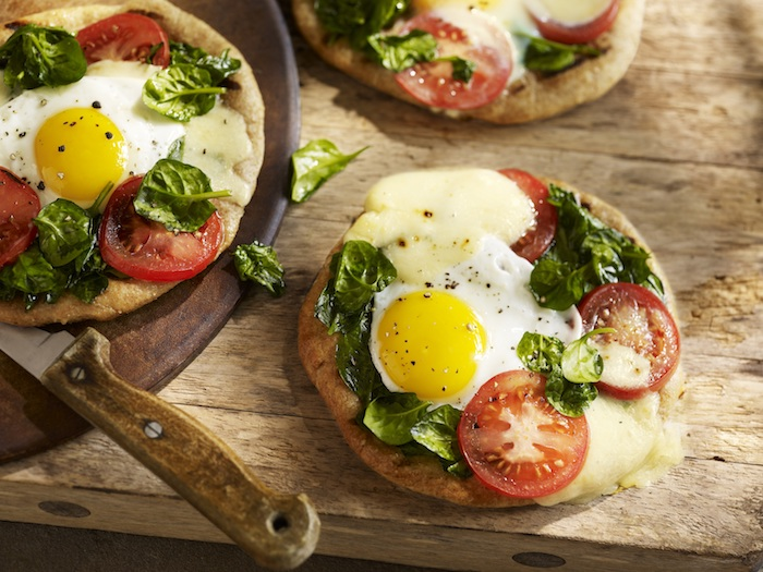 massive wooden table, with a cutting board and a knife, and three flatbreads, topped with cheese, tomato slices and basil leaves, and a baked egg, easy breakfast recipes