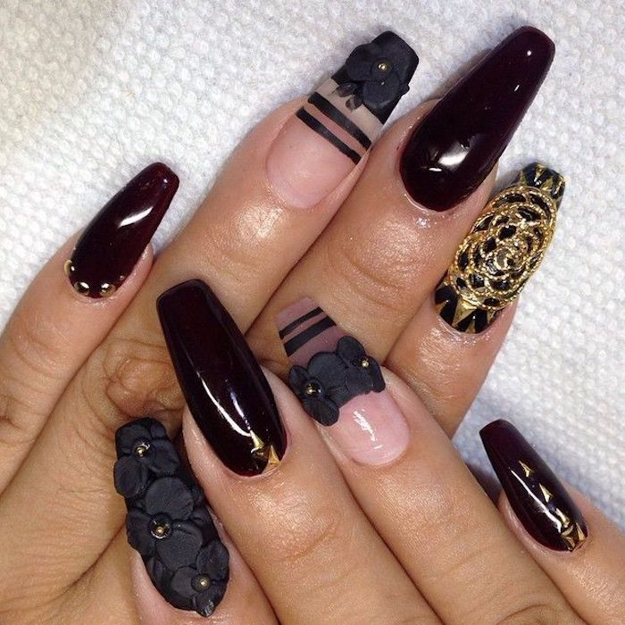 flowers made from black acrylic, decorating a manicure, with clear and very dark cherry red nail polish, coffin nail designs, with black stripes and gold motifs