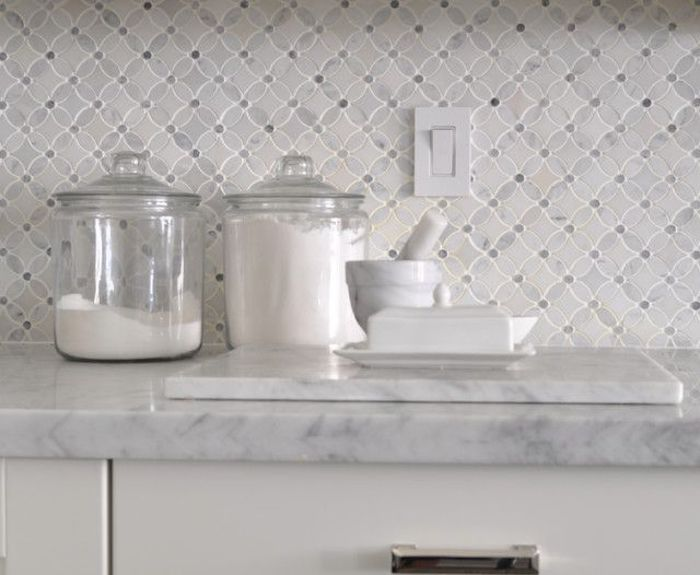 clear glass jars with lids, containing salt of flour, on a light marble counter top, near a small mortar and pestle, white and pale grey arabesque tile backsplash