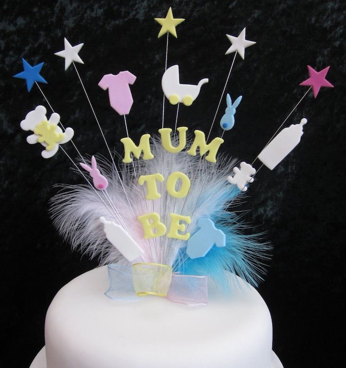 mum to be written in yellow, on a cake topper, with pale blue, yellow and pink ribbon, light colored feathers, and various baby-related shapes