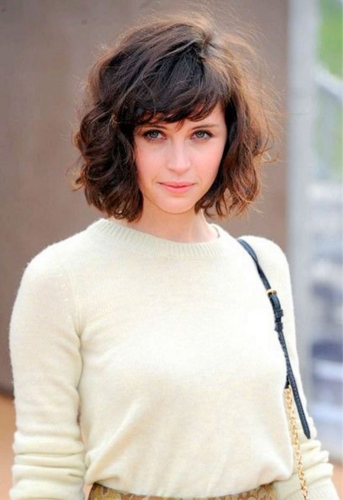 sweater made from fluffy, cream colored fabric, worn by young woman, with blue eyes, and brunette hair, with side bangs, short haircuts for curly hair