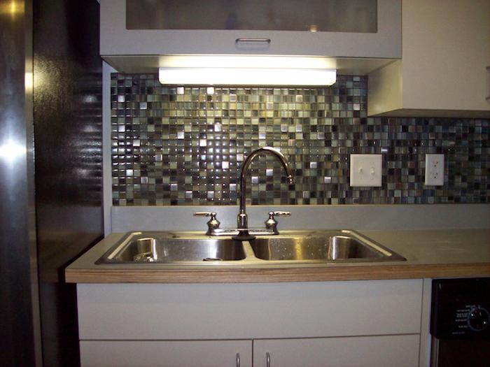 rectangular lit fluorescent lamp, near a stone and glass mosaic tile backsplash, in different shades of grey, metal sink and a light wooden counter top