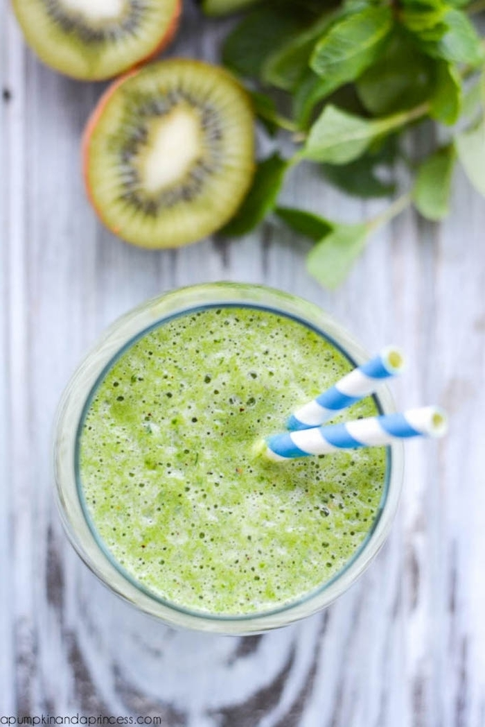 kiwi pieces and mint leaves, on a grayish wooden surface, near a clear glass, filled with foamy green liquid, healthy breakfast ideas, two paper straws