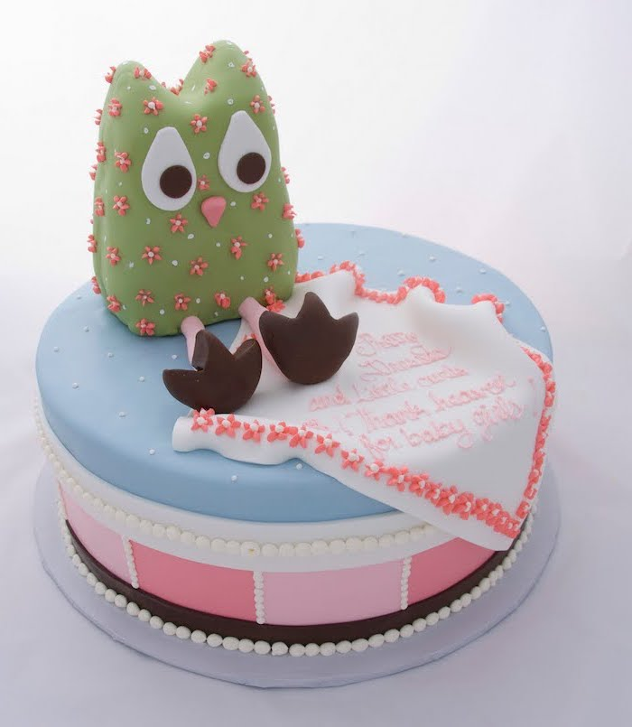 green owl figurine, with big white eyes, decorated with a pink and white floral pattern, on top of a blue and pink cake, owl baby shower cake, with a festive message, done in peach-colored frosting
