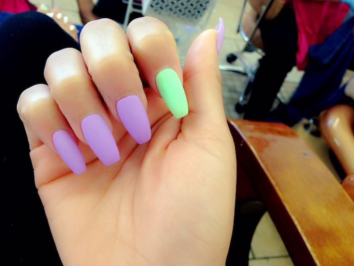accent nail in neon green, and four other nails in neon purple, on a hand with folded fingers, matte coffin nails