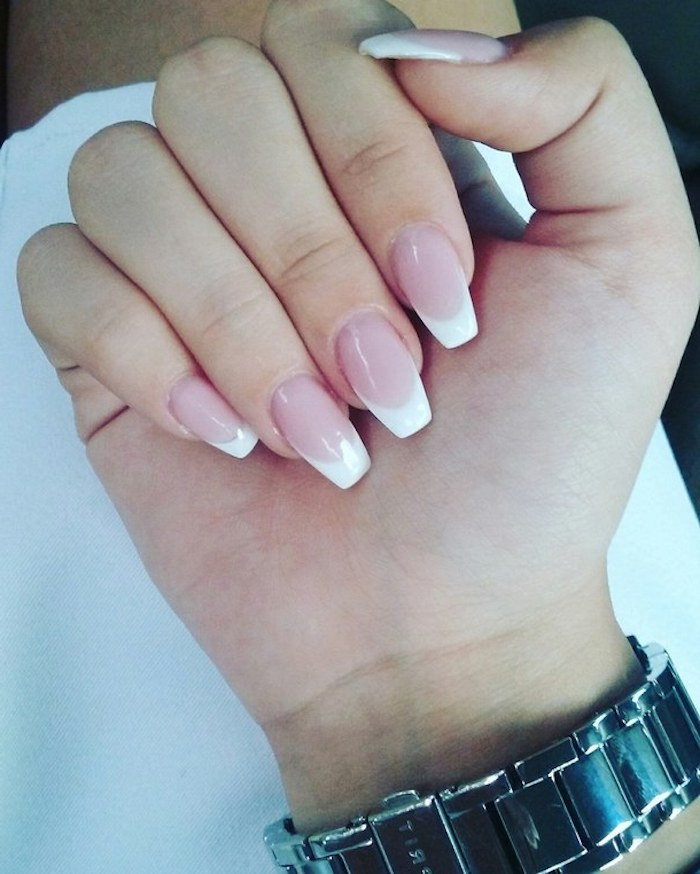square tips on medium long, oval nails with french-style manicure, pale pink base, and white tips, on a hand with folded fingers
