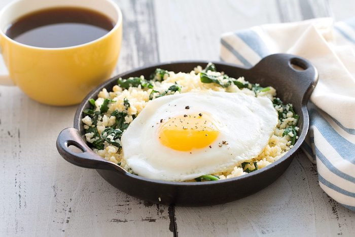 cup of tea or coffee, what is a healthy breakfast, next to a pan, filled with couscous and green veggies, and topped with a large fried egg