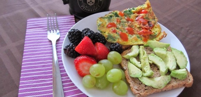 blackberries and strawberries and grapes, near a piece of toast, covered with avocado slices, and a piece of vegetable frittata