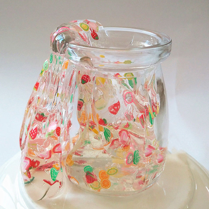 clear slime decorated with many colorful stickers, shaped like different fruit, pouring out of a clear glass jar, placed on an upturned white plate