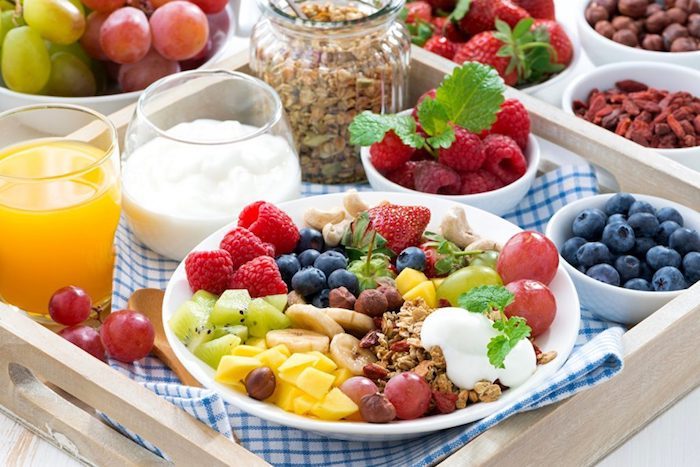 mango and kiwi pieces, banana slices and grapes, and strawberries and raspberries, in a white ceramic plate, with a dollop of yoghurt, and some muesli