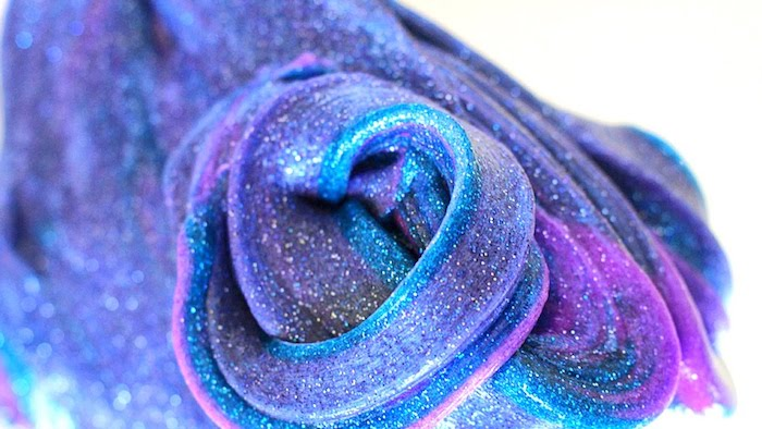 fine powdery glitter, decorating a twisted piece, of galaxy-inspired elmer's glue slime, in violet and purple, with blue streaks