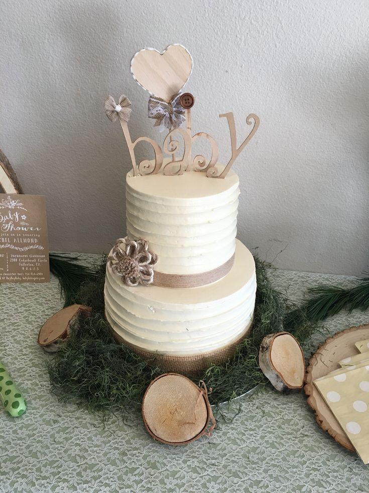 beige and cream cake, decorated with a topper reading baby, and surrounded by pine branches, and little wooden decorations