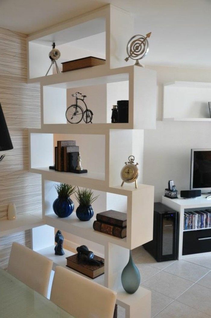 shelves in white, containing books and vases, and various decorative items, how to decorate a living room, tv on a white and black stand, in the background