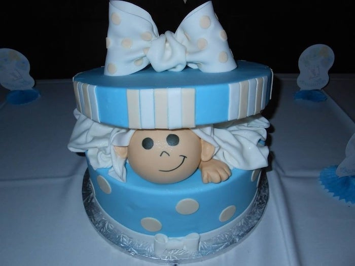 round cake shaped like an open blue present, with cream and white stripes, a big pale blue bow, and a baby peeking from within