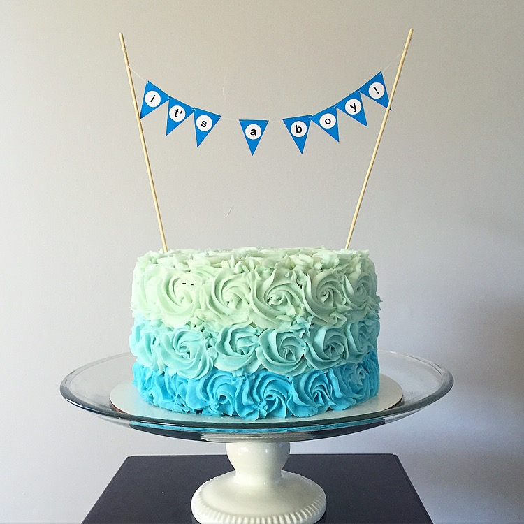 roses made from frosting, in teal and turquoise and pale minty green, on a cake decorated with tiny blue flags, spelling the words it's a boy, baby shower cakes for boys, glass cake stand