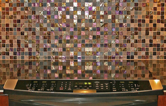 iridescent glittering mosaic tiles, in grey and pink, blue and purple, on a kitchen wall, near a smooth, dark counter top, glass mosaic tile backsplash