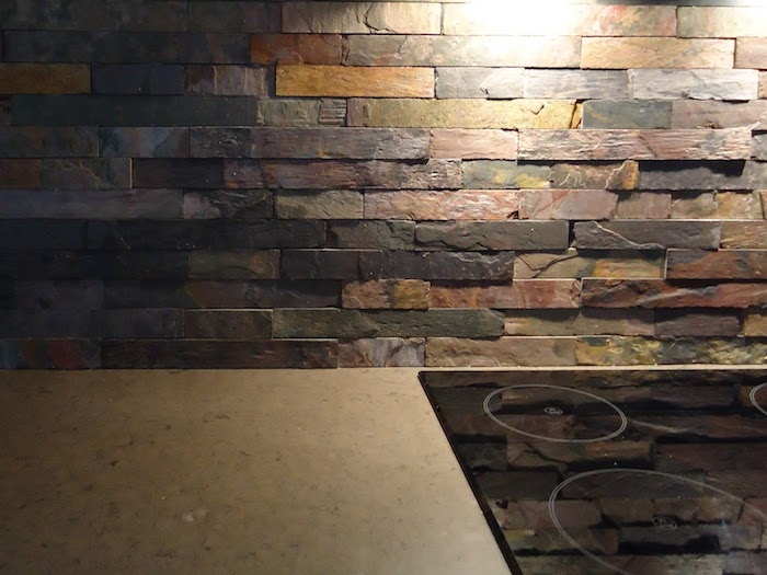 orange and brown, beige and grey, pieces of stone, forming a stacked stone backsplash, near a smooth black hob, and a beige countertop