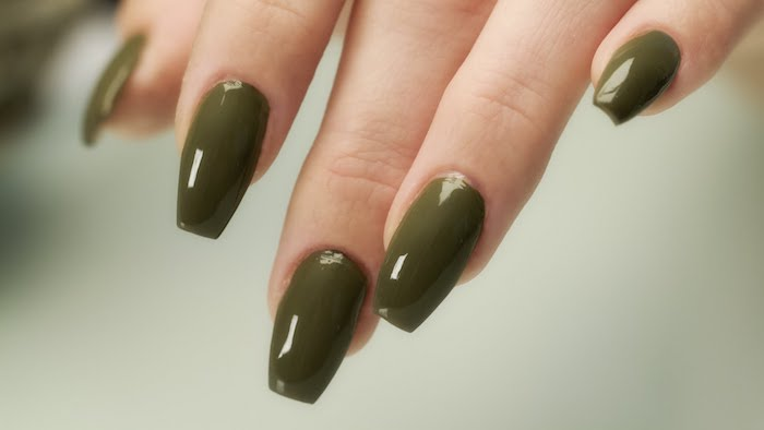 coffin shaped nails, painted in olive green, smooth and glossy nail polish, on the fingers of a hand, seen in close up