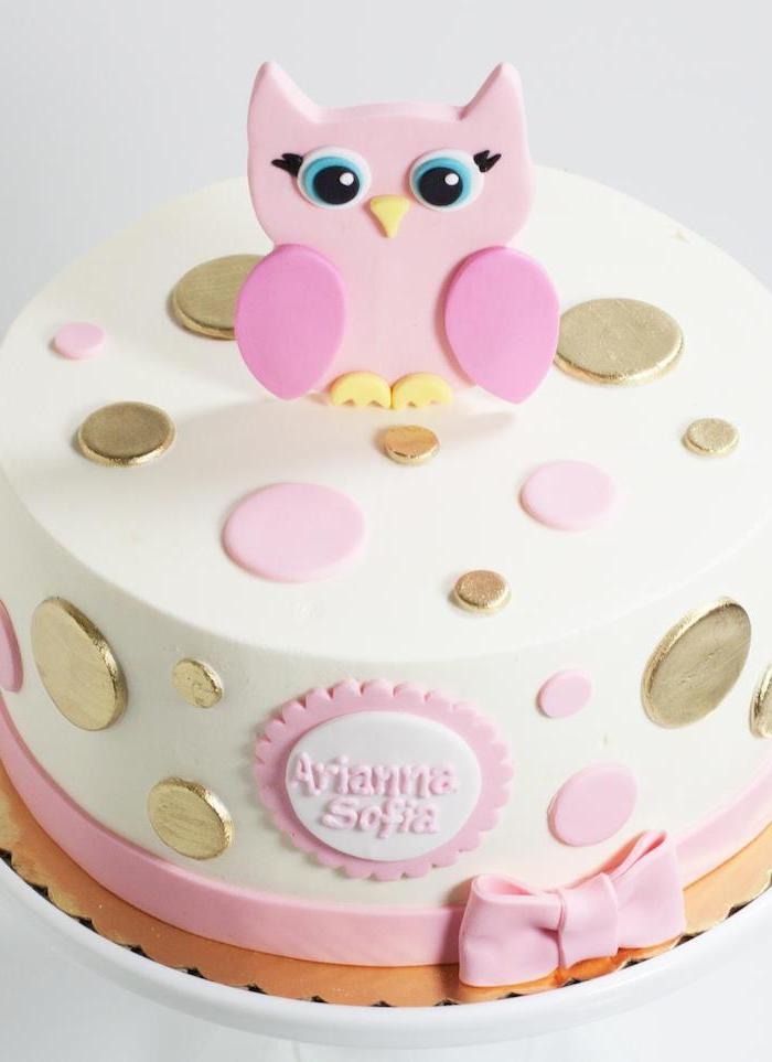 buttons in metallic gold, and pale pink colors, decorating a white cake, topped with a pink owl figurine, owl baby shower cake, the name arianna sofia, written in pink