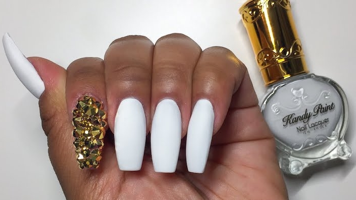 coffin acrylic nails, painted in white matte nail polish, the index finger nail, is covered in gold rhinestones, bottle of white nail polish nearby