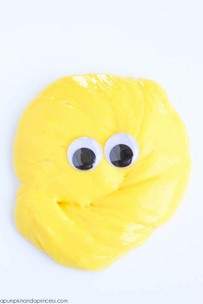 slime recipe without borax, yellow glob of goo, placed on a smooth white surface, and decorated with two googly eye stickers, in black and white
