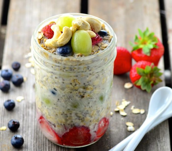 cashew nuts and blueberries, grapes and strawberries, on top of a clear glass jar, containing milk and oats, best breakfast for weight loss, more strawberries and blueberries nearby
