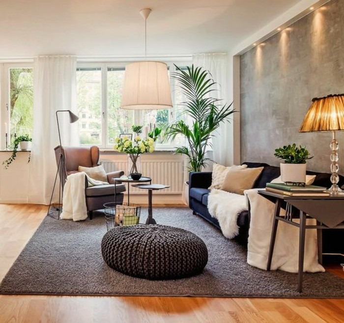 navy blue sofa, with two beige cushions, and a white fluffy throw, how to decorate a living room, beige armchair and a large, green potted plant, antique orange lamp