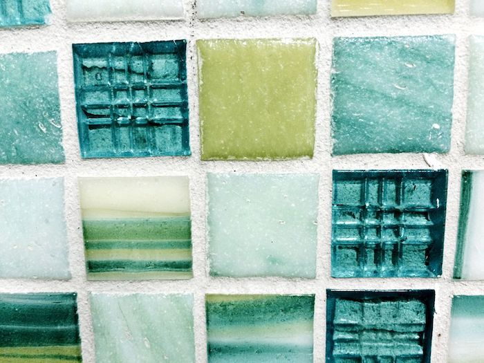 opaque and transparent, pale blue and green square tiles, some with stripes, in a glass mosaic tile backsplash, seen in extreme close up