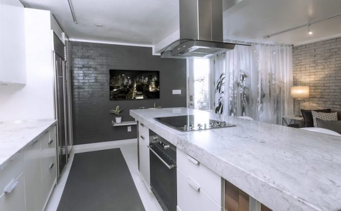 dark and light grey brick walls, in a modern kitchen, with pale grey marble countertop, fridge and cooker, potted plants and a lit lamp