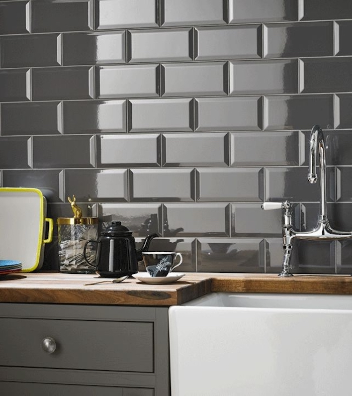 reflective and glossy, grey subway tile back splash, near a wooden counter top, with an inbuilt white sink, and grey cabinets