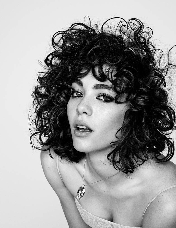shaggy shoulder-length, dark brunette hair with curly bangs, hairstyles for short curly hair, worn by woman with black eye make up, seen in a black and white image