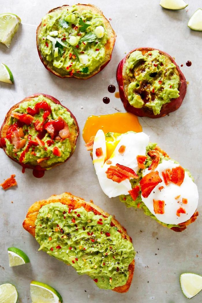 five different piece of bread, with guacamole spread, garnished with different toppings, low calorie breakfast, pepper and eggs, chili flakes and parsley