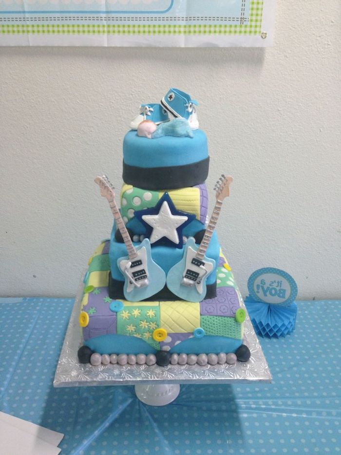 sneakers in white and blue, and a small sleeping baby figurine, in a pale blue onesie, topping a colorful patchwork cake, decorated with two blue fondant guitars