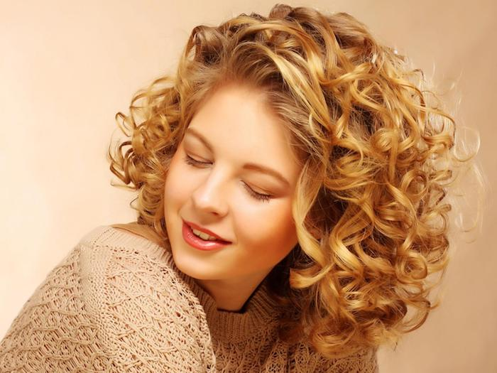 beige knitted top, on woman with closed eyes, wearing glossy pink lipstick, side parted and curled blonde hair, hairstyles for short curly hair