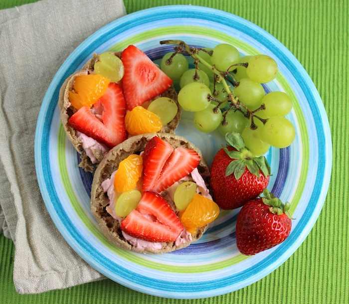 pink yoghurt spread, on two pieces of bread, garnished with chunks of strawberry, orange and grape, easy breakfast recipes, in a plate with strawberries, and more grapes