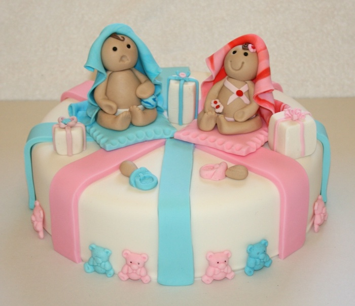 frowning and smiling baby figurines, one covered in a blue blanket, and one in a striped, red and pink blanket, twin baby shower cakes, smooth white cake with fondant decorations